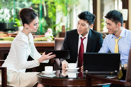 Three business people discussing in meeting at office desk Stock Photo