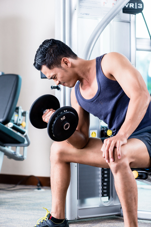 Young man doing dumbbell biceps curls at gym Stock Photo