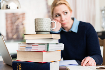Mug on stack of books in front of contemplated woman