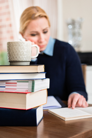 Stack of books with mug on top in front of woman reading book Stock Photo