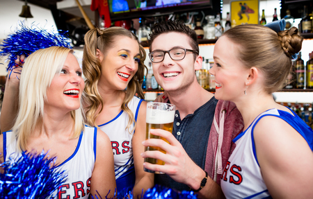 Fans of a sports team watching game in bar drinking beer