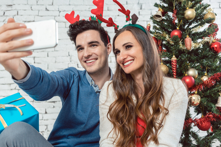 Couple making selfie photos with phone on Christmas for sharing in social media