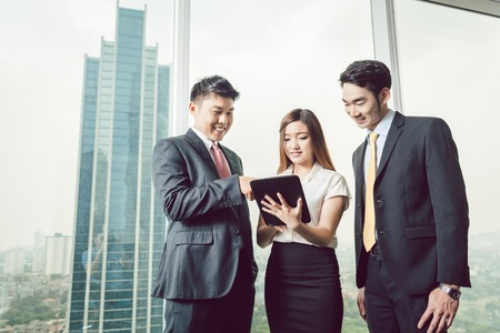 Portrait of businesspeople standing near the window looking at digital tablet Stock Photo