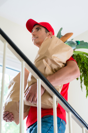 Close-up of happy delivery man in red uniform carrying grocery shopping bags Stock Photo