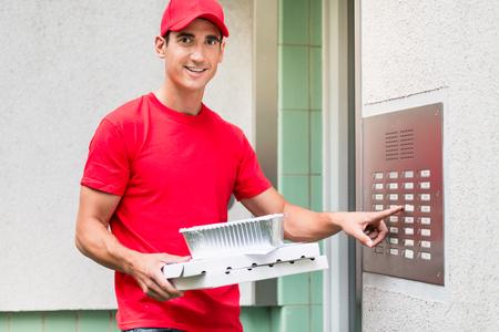 Pizza delivery man in red uniform carrying boxes using the intercom at door