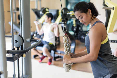 Side view of a determined young woman exercising cable rope triceps extension during upper-body workout routine in a modern fitness club