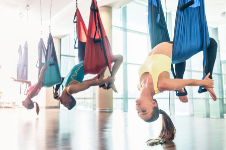 Side view of a fit and beautiful young woman hanging upside down while practicing aerial yoga during group class in a modern fitness club Stock Photo
