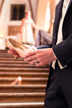 Close-up of bridegrooms hand holding brides wedding shoe in front of staircase Stock Photo