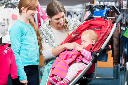 Close-up of happy girl looking at mother taking care of baby sitting in carriage at shop