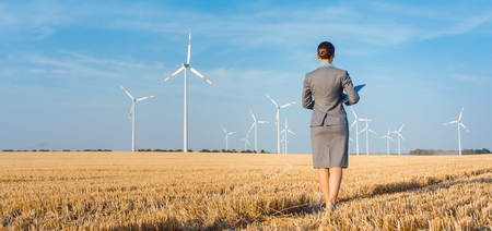 Investor in green energy looking at her wind turbines standing with suit on field Stock Photo
