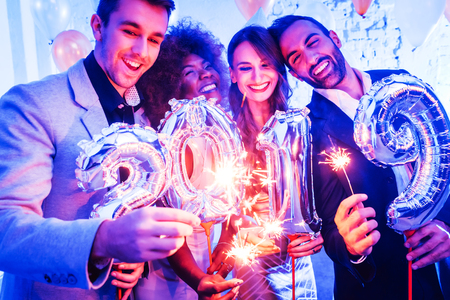 Men and women celebrating the new year 2019 with sparklers and wine Stock Photo