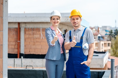 Architect and Construction worker on site giving thumbs-up to the camera Stock Photo