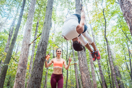 Man and woman doing functional fitness and sport in outdoor gym