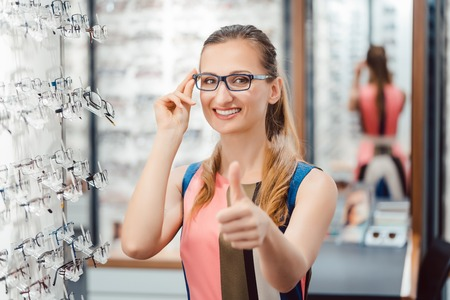 Woman recommending buying new eyewear giving a thumbs up