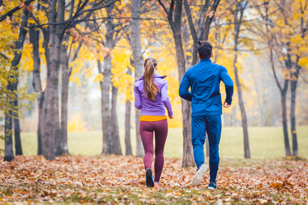 Couple jogging or running in colorful foliage, seen from behind Stok Fotoğraf - 110440166