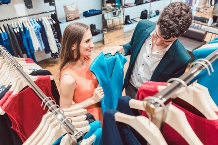 Woman convincing her partner of buying a new dress in hip high fashion store