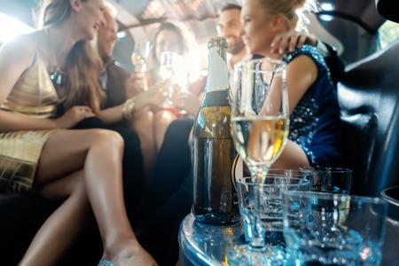 Frauen und Männer, die mit Getränken in einem Limousinenauto feiern, konzentrieren sich auf die Alkoholflasche