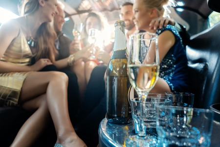 Women and men celebrating with drinks in a limousine car, focus on the alcohol bottle