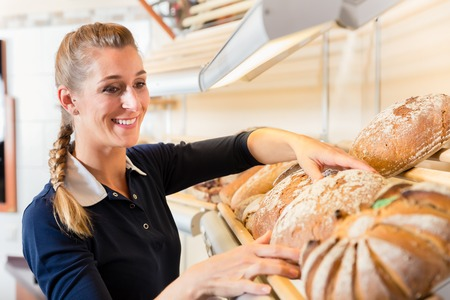 Bakery woman putting bread in shop shelf to sell it