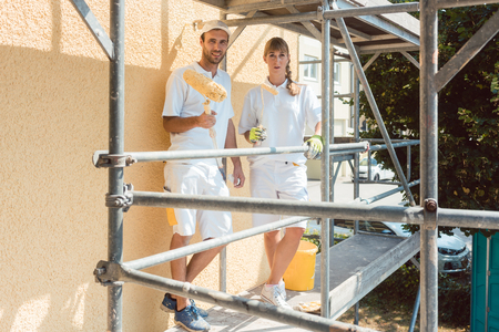 Two painters on scaffold looking into the camera being proud of their work Zdjęcie Seryjne