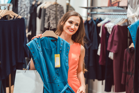 Woman pondering buying a blue dress in fashion store looking at herself in mirror