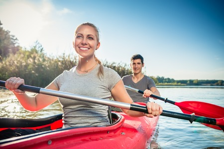 Smiling young woman kayaking with her boyfriend on lake Stock fotó