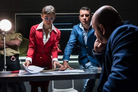 Low-angle view of two persuasive investigators trying to obtain a signed confession from a reluctant suspect at the police station Stock Photo