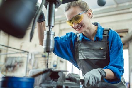 Trabajadora en taller metalúrgico con taladro de pedestal para trabajar en la pieza