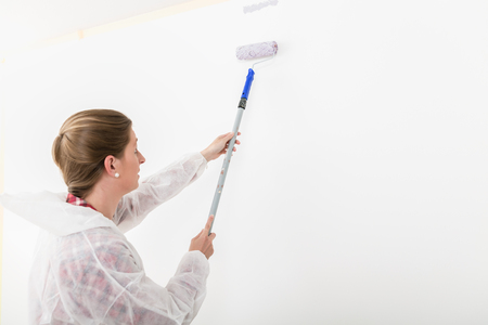 Side view of woman wearing workwear painting with anchor roller on white wall Standard-Bild - 110736523