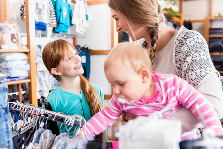 Close-up of happy mother shopping with her daughter and baby son Standard-Bild