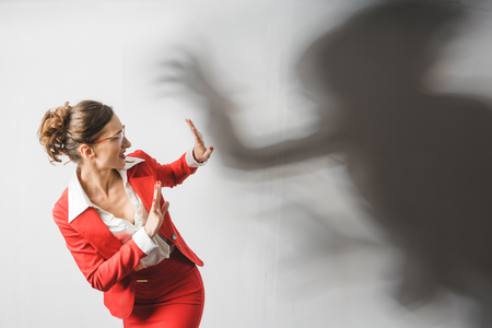 Businesswoman in red suit being harassed, symbolic picture with shadow