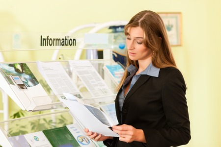 Young businesswoman standing in front of rack reading information leaflet
