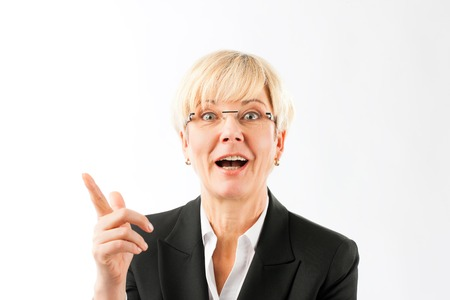 Close-up of happy mature businesswoman pointing finger against white background