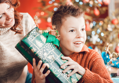 Christmas, happy family, son and mother, unwrapping presents under the tree Stock Photo