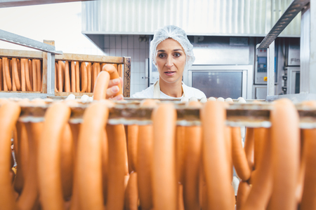 Ring Sausages in rack waiting to be smoked in butchery, woman looking over it Stockfoto