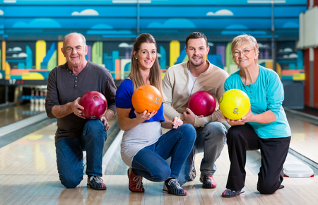 Happy family with multi colored bowling ball posing in alley Standard-Bild