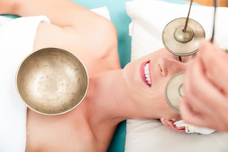 Woman in spa setting having a singing bowl massage therapy