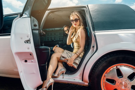 VIP Woman and man getting out of limousine with door being open Reklamní fotografie