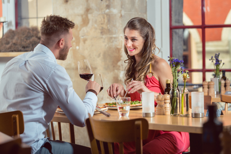 Happy young couple eating food with red wine at restaurant Foto de archivo