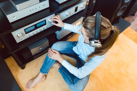 Woman with headphones listening to music via the Hi-Fi stereo in her home Stock Photo