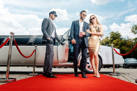 Coppia in arrivo con la limousine che cammina sul tappeto rosso, un autista sta aprendo la portiera della macchina Archivio Fotografico