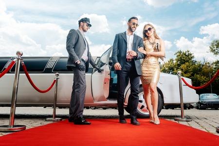 Echtpaar arriveert met limousine lopende rode loper, een chauffeur opent de autodeur Stockfoto