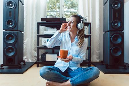 Frau, die zu Hause Musik von einer Hi-Fi-Stereoanlage hört Standard-Bild