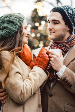 Couple with cups of mulled wine as drink on Christmas market Imagens