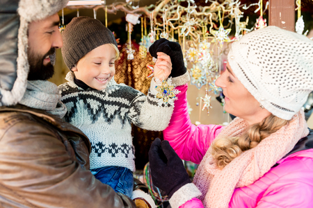Family on Christmas market buying ornaments and baubles to decorate the tree
