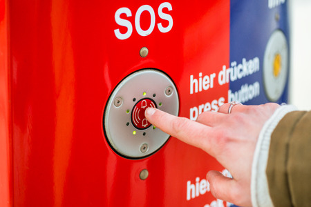 Woman pressing SOS emergency button in train station, only finder to be seen Stock fotó