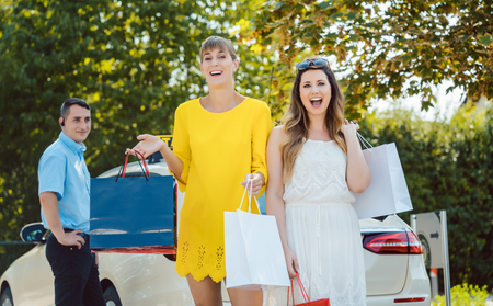 Best woman friends getting out of taxi from shopping trip in town