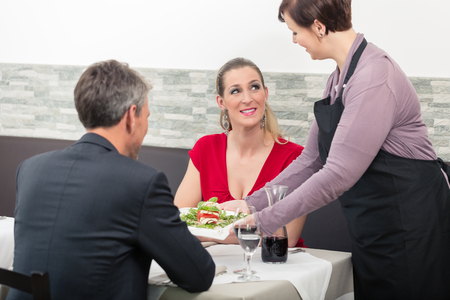 Female waitress placing order in front of couple