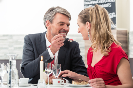Man feeding his wife during candle light date Stock Photo
