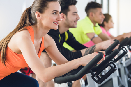 Side view of a smiling woman exercising on bicycle at the fitness center Stock Photo